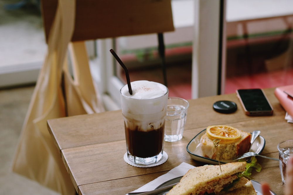 clear drinking glass with latte on brown wooden table