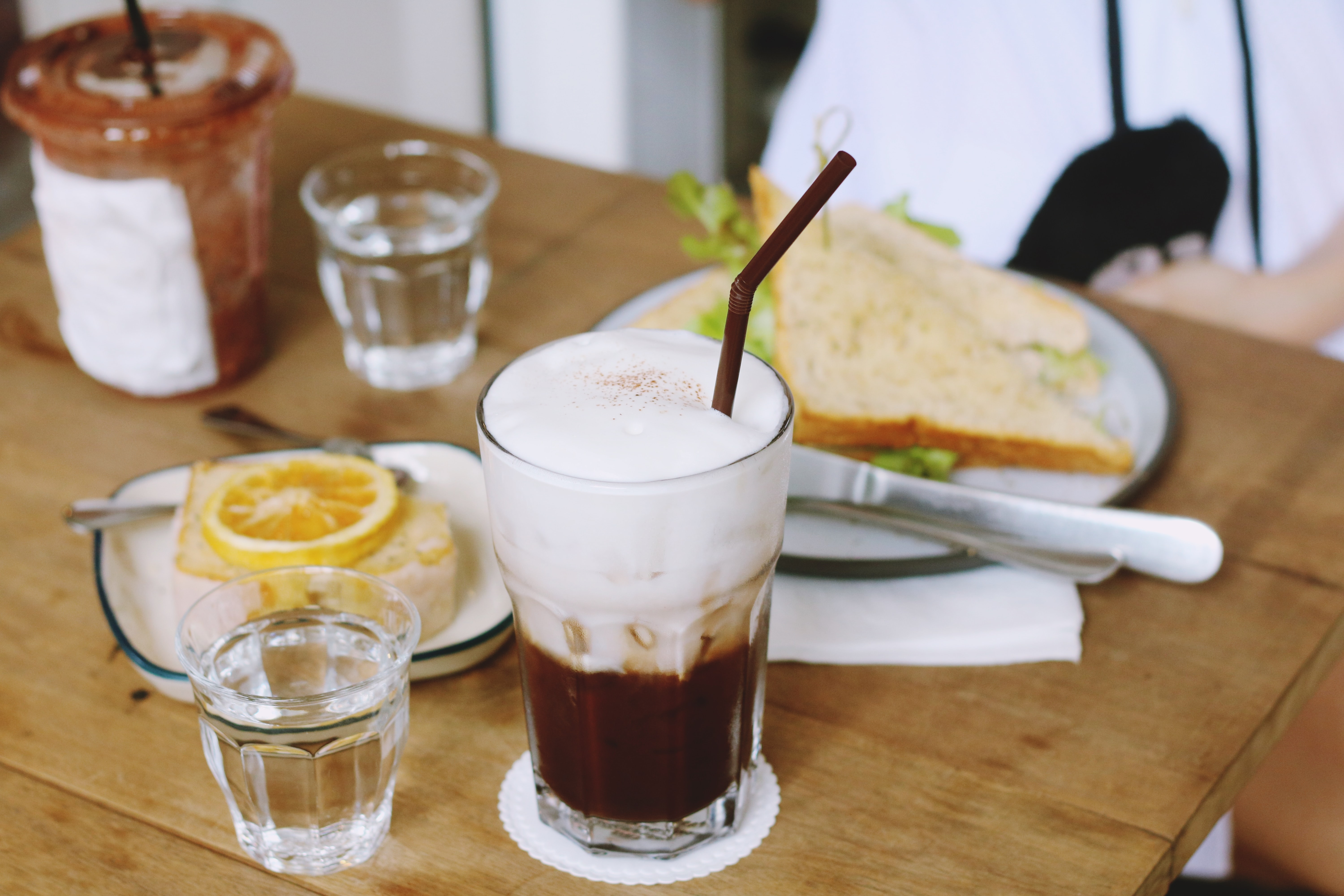 clear drinking glass filled with brown liquid in front of plate sandwich on table