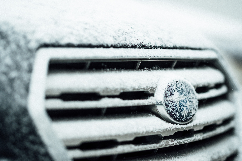 selective-focus photography of black Subaru emblem