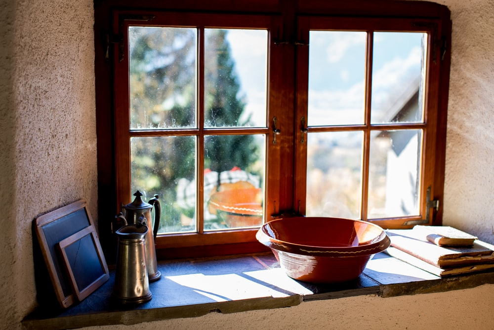 brown ceramic bowl near brown wooden window pane at daytime