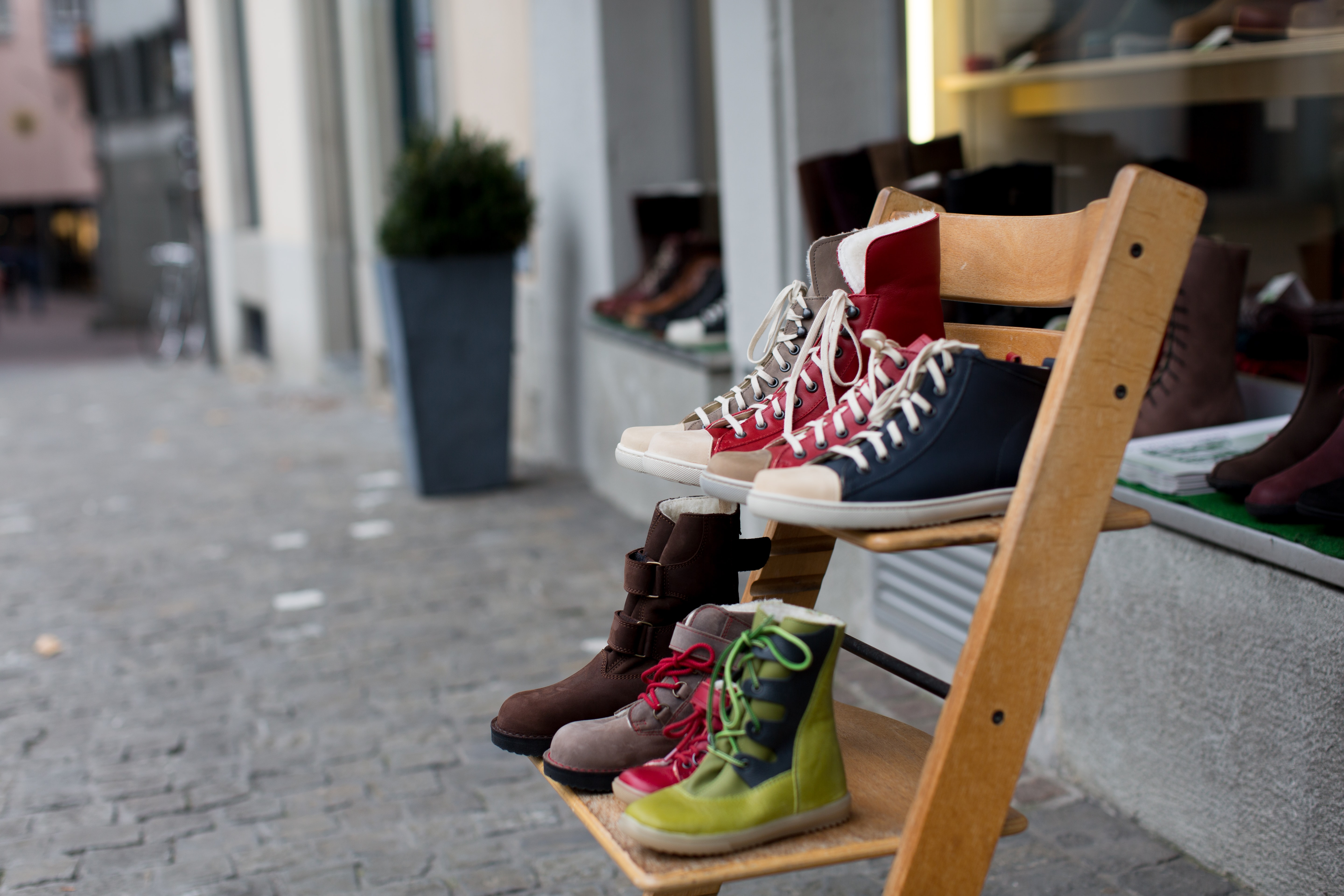 assorted-color pairs of footwear on brown wooden 2-layer shoe rack