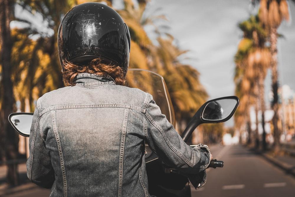 woman wearing grey denim jacket riding motorcycle during daytime