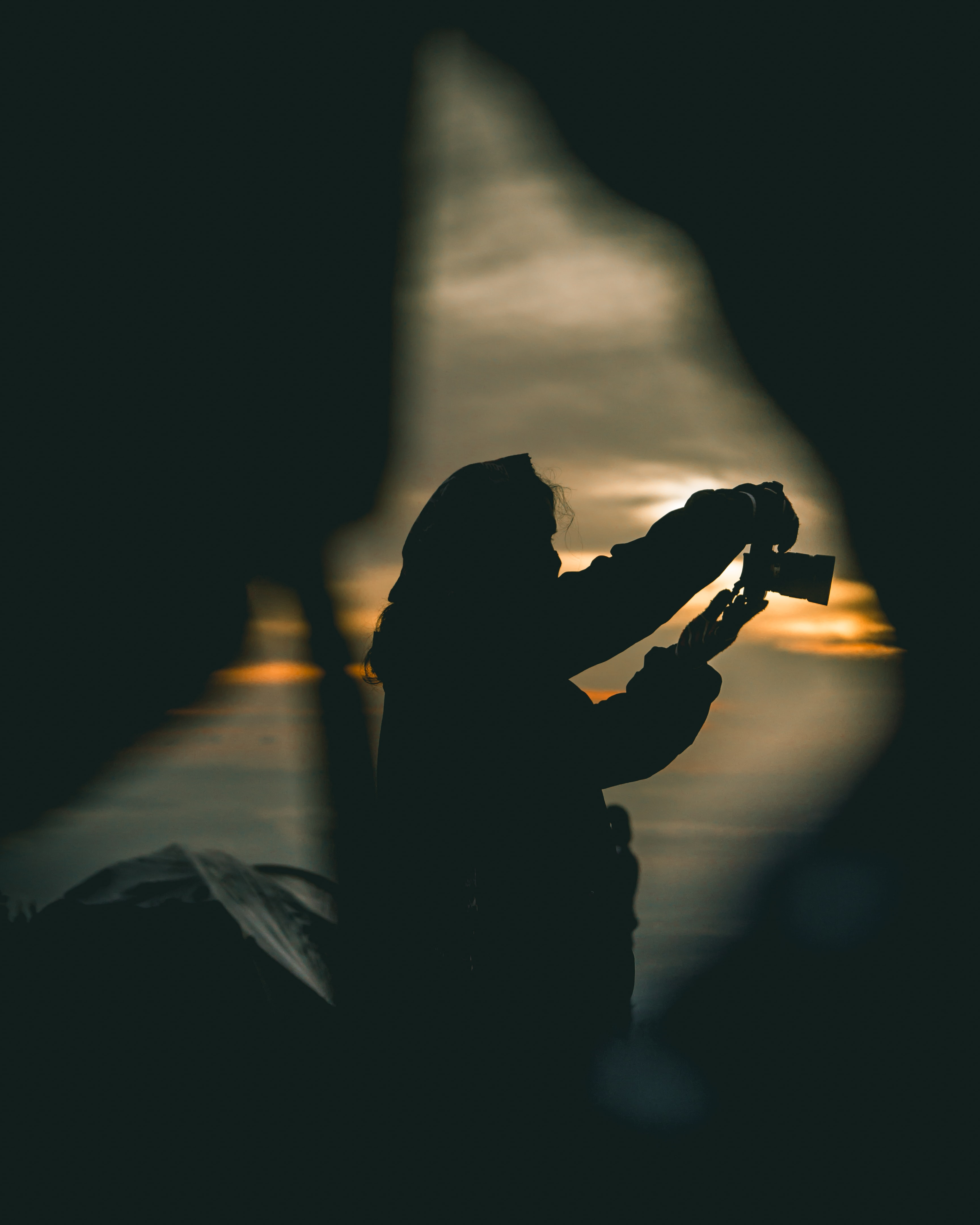silhouette of person holding camera during orange sunset