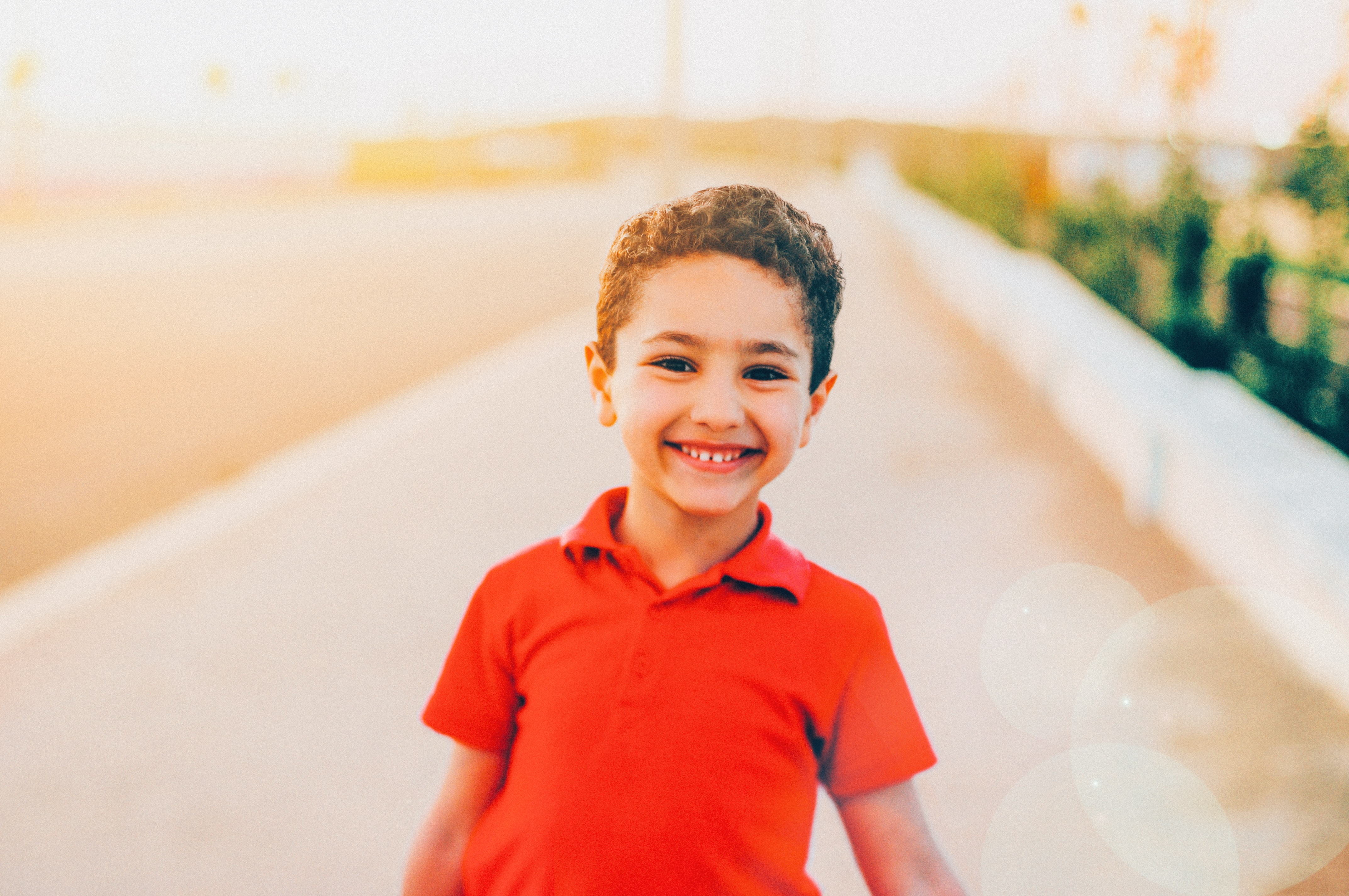 smiling boy wearing red polo shirt