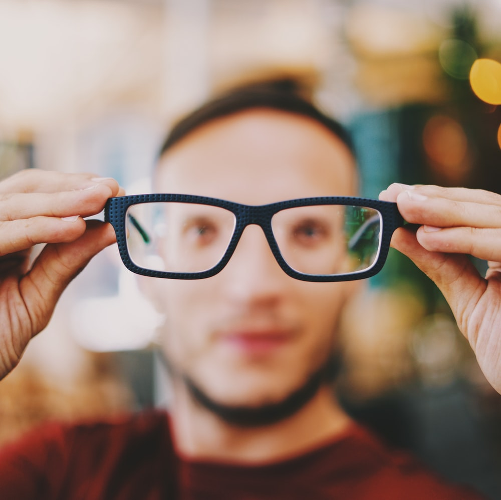 person holding eyeglasses with black frames