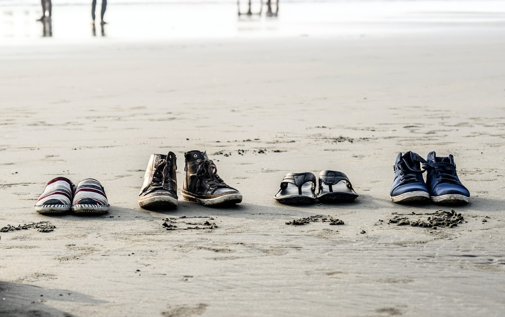 two pair of shoes and flip-flops on seashore near people at daytime