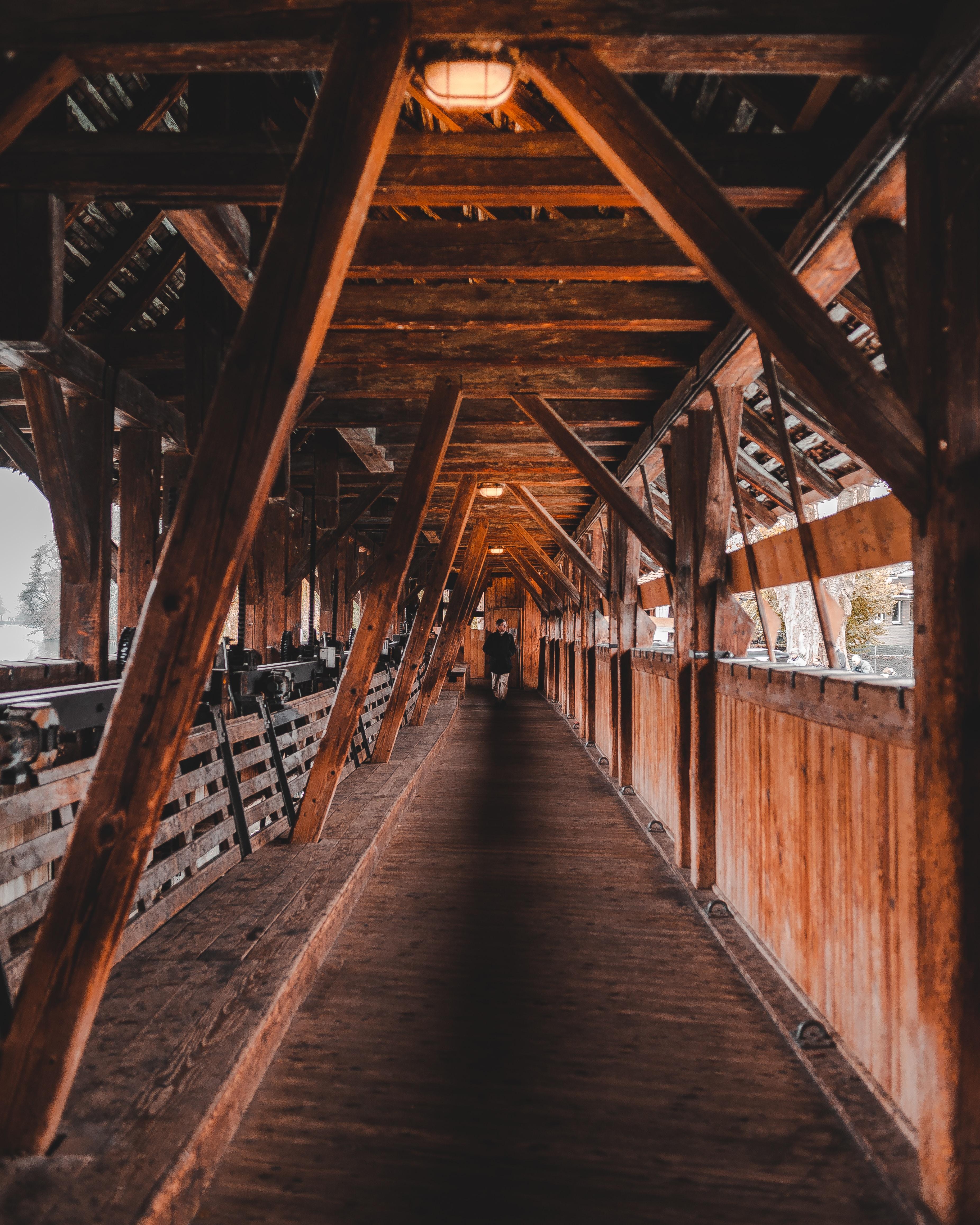 man walking on wooden bridge