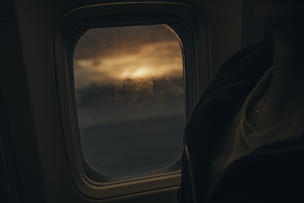 silhouette photo of person sitting beside plane's window
