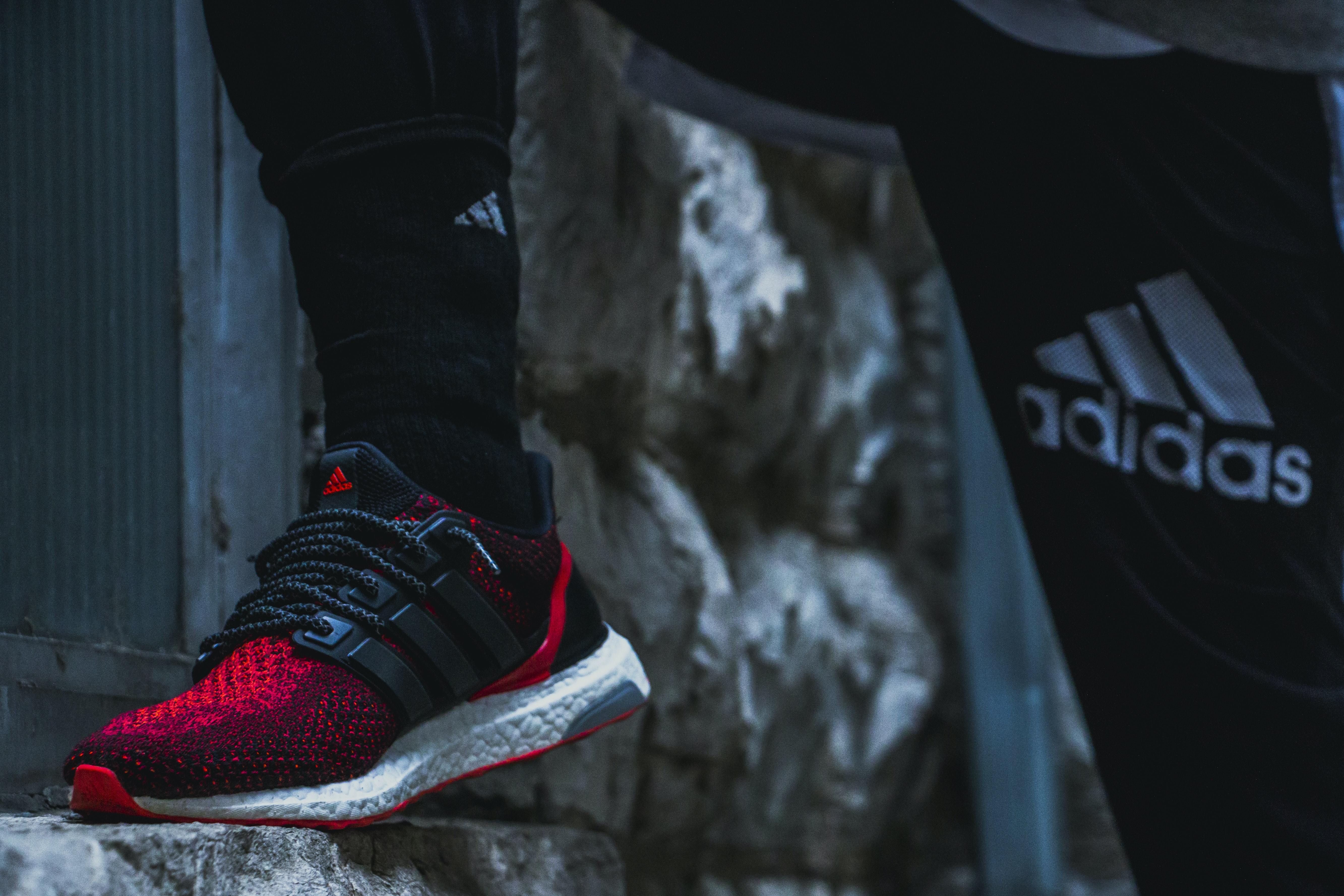 person wearing red and black adidas shoes