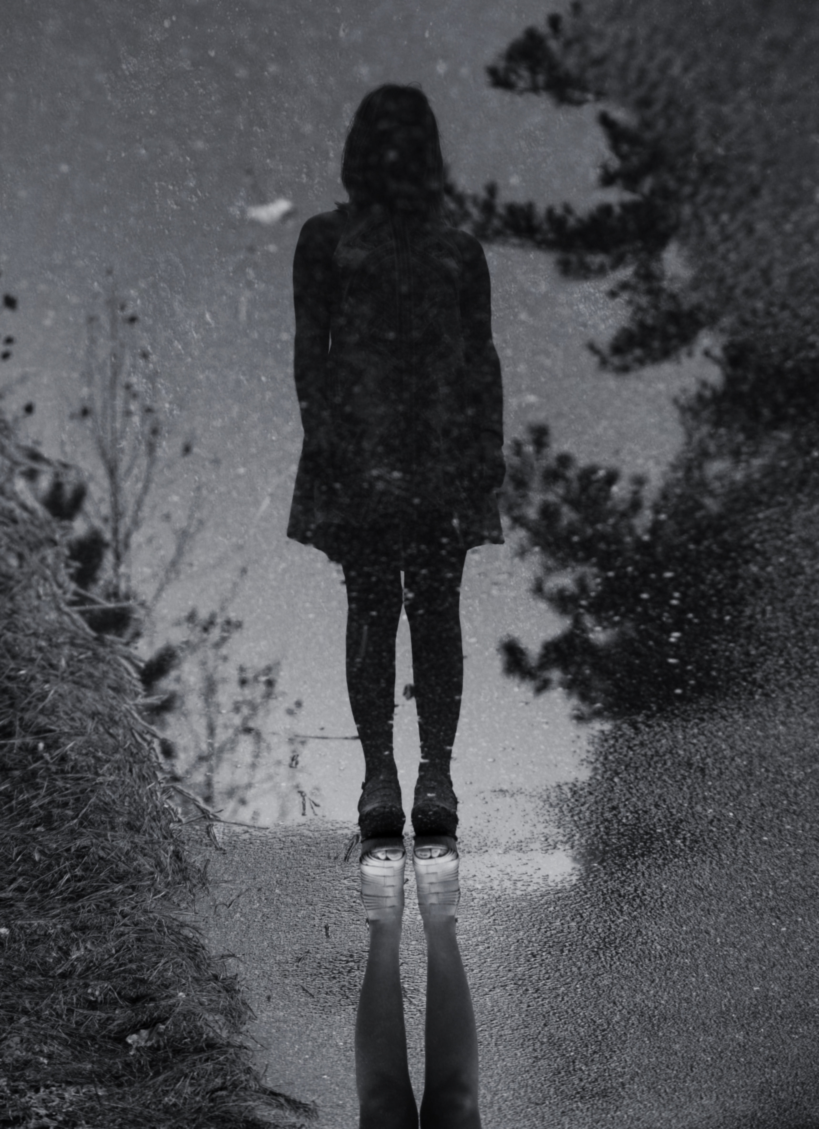 grayscale photo of person standing reflects on water near trees