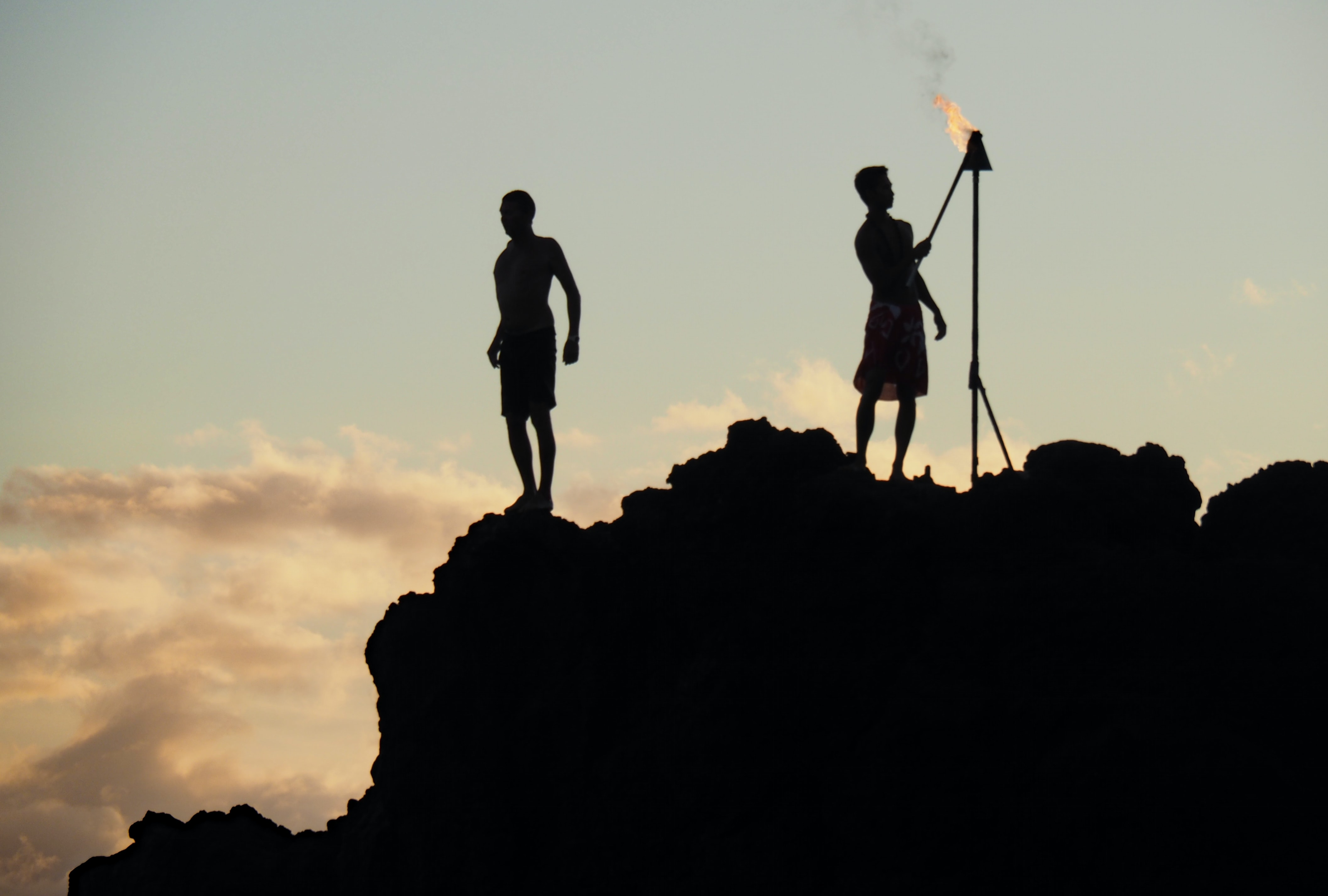 silhouette photo of man holding fire stick near man standing at peak of mountain