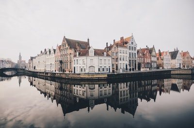 white and brown concrete buildings near bodies of water belgium teams background