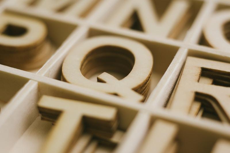 pile of Q cardboard cutout in organizer selective focus photo