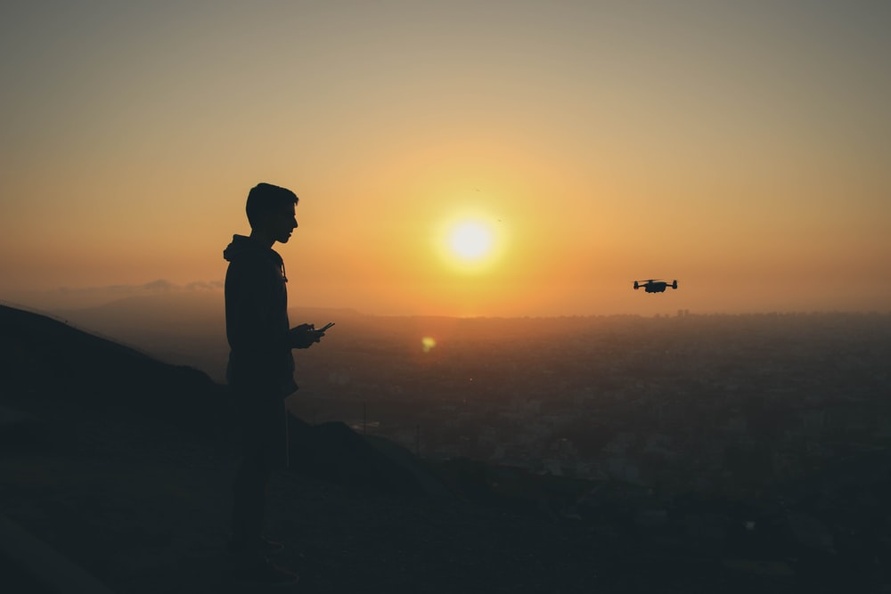 silhouette photo of man holding drone remote