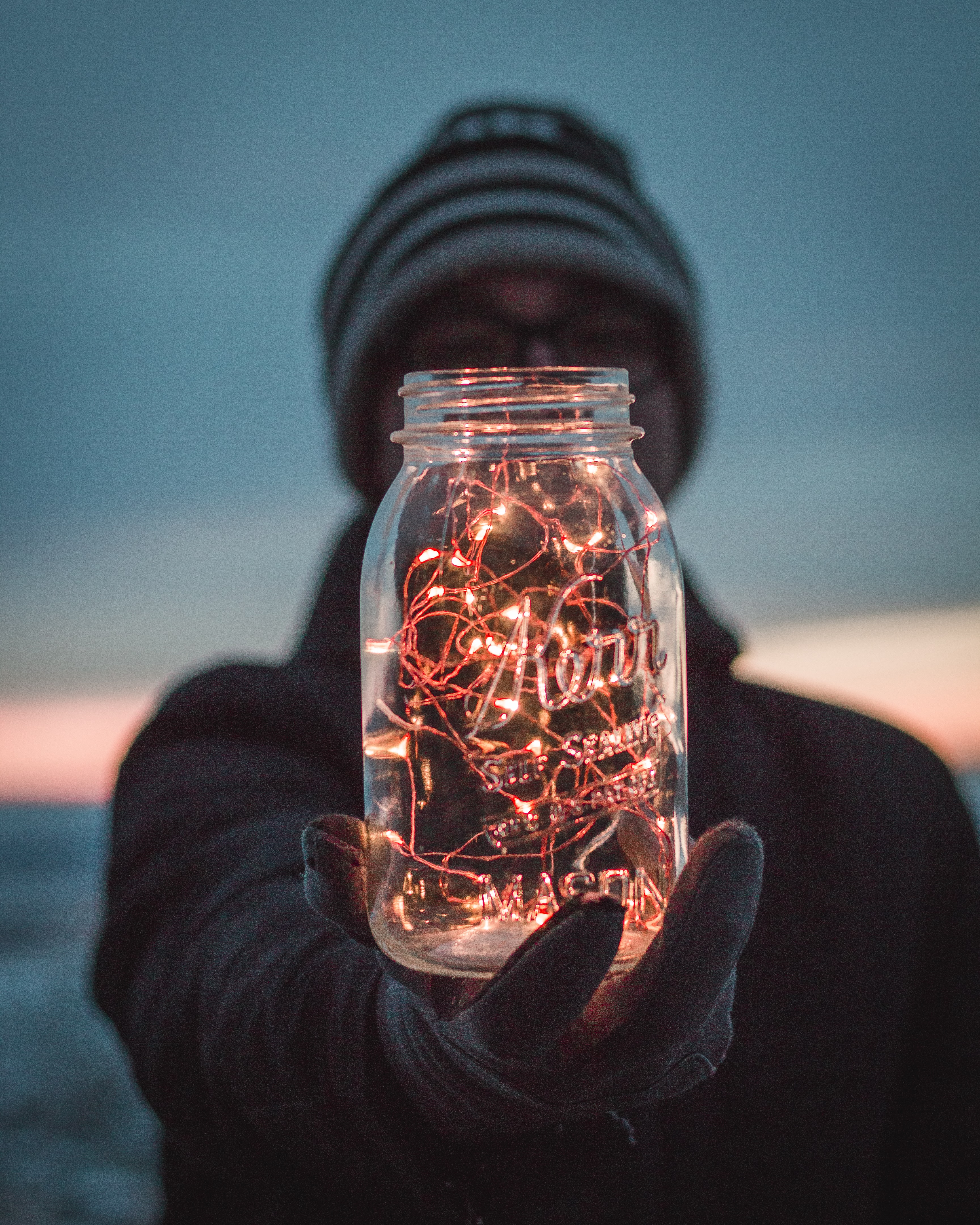 person holding glass mason jar with string lights