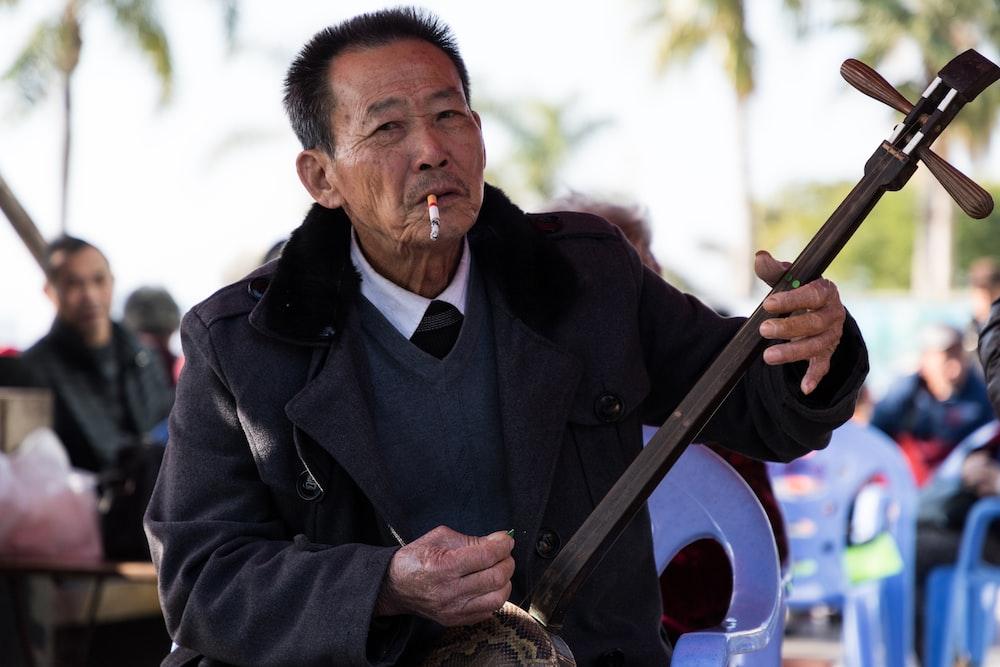 man wearing black suit holding guitar while smoking