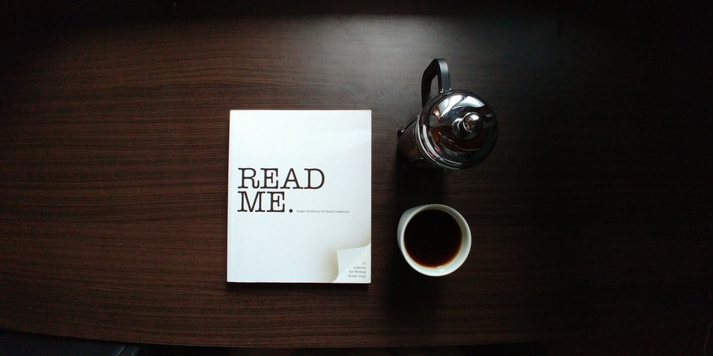 flat-lay photo of Read Me. book beside cup and silver mug on table