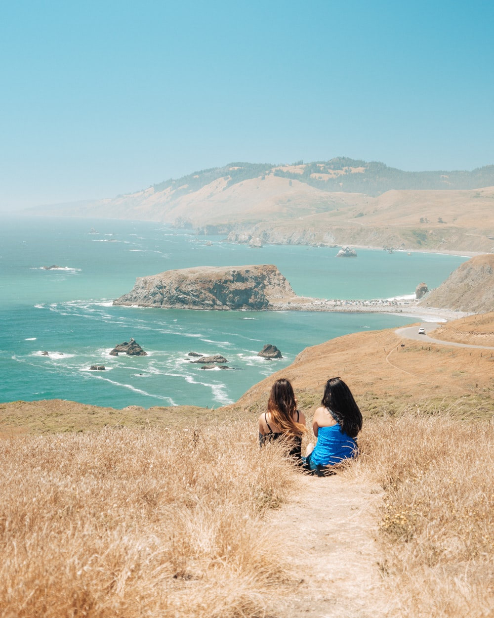 two women sitting on brown grass facing mountain and sea water