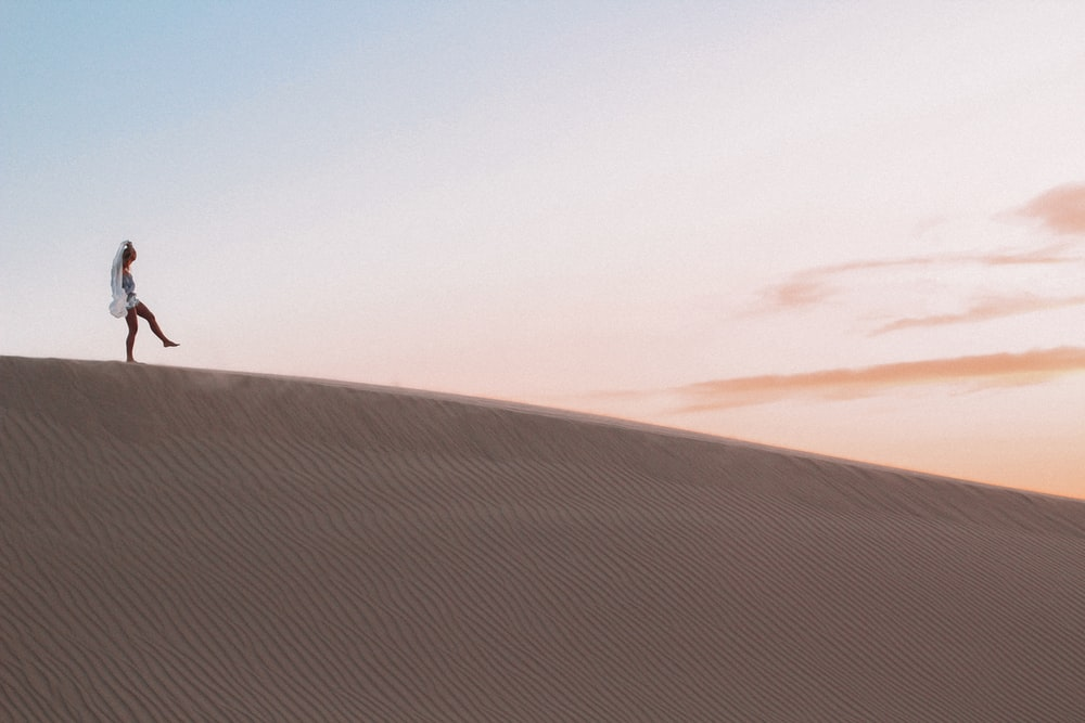 photo of person walking along desert