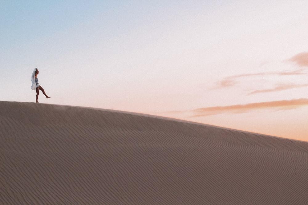 photo of person walking along desert