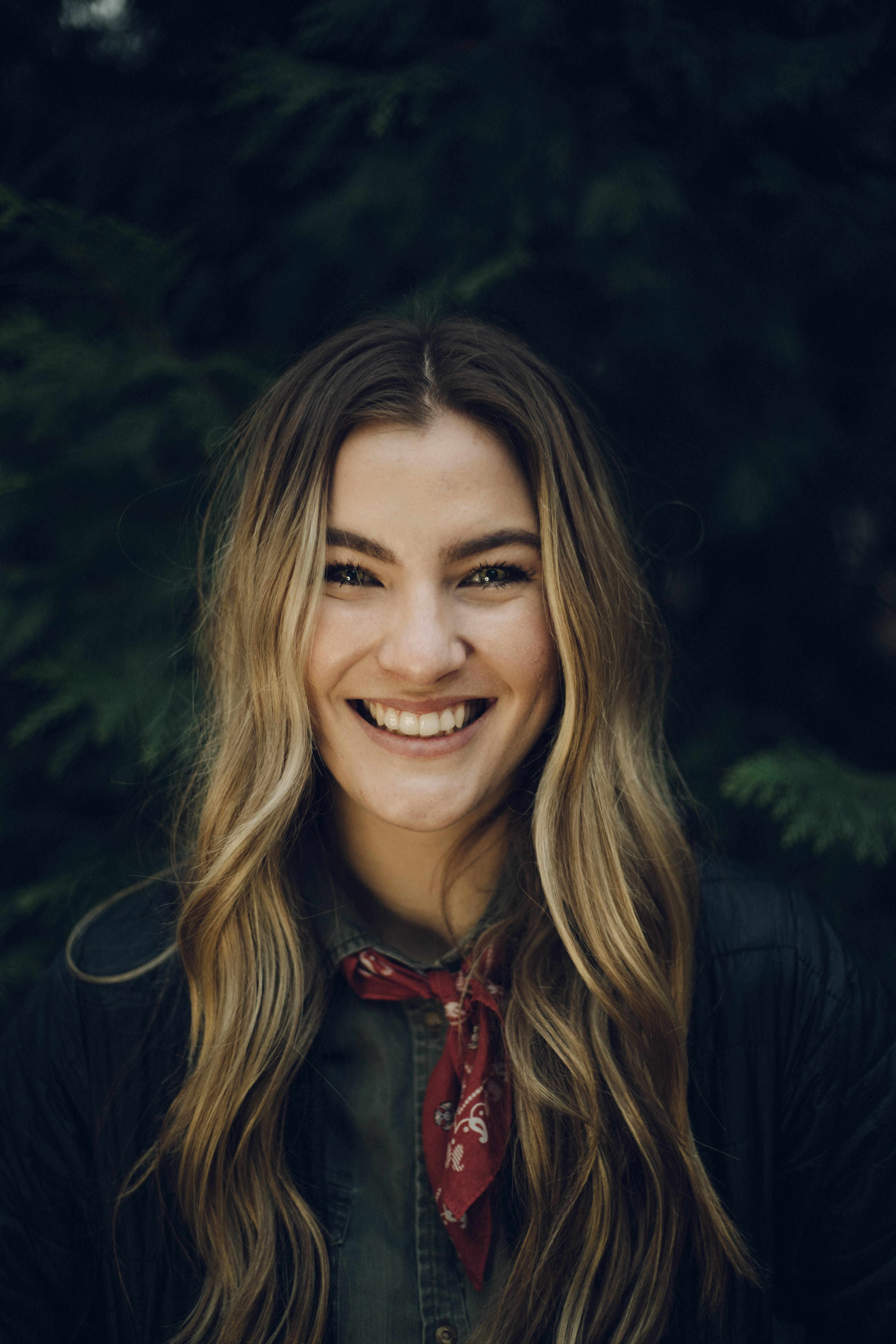 selective focus photography of smiling woman wearing button-up shirt