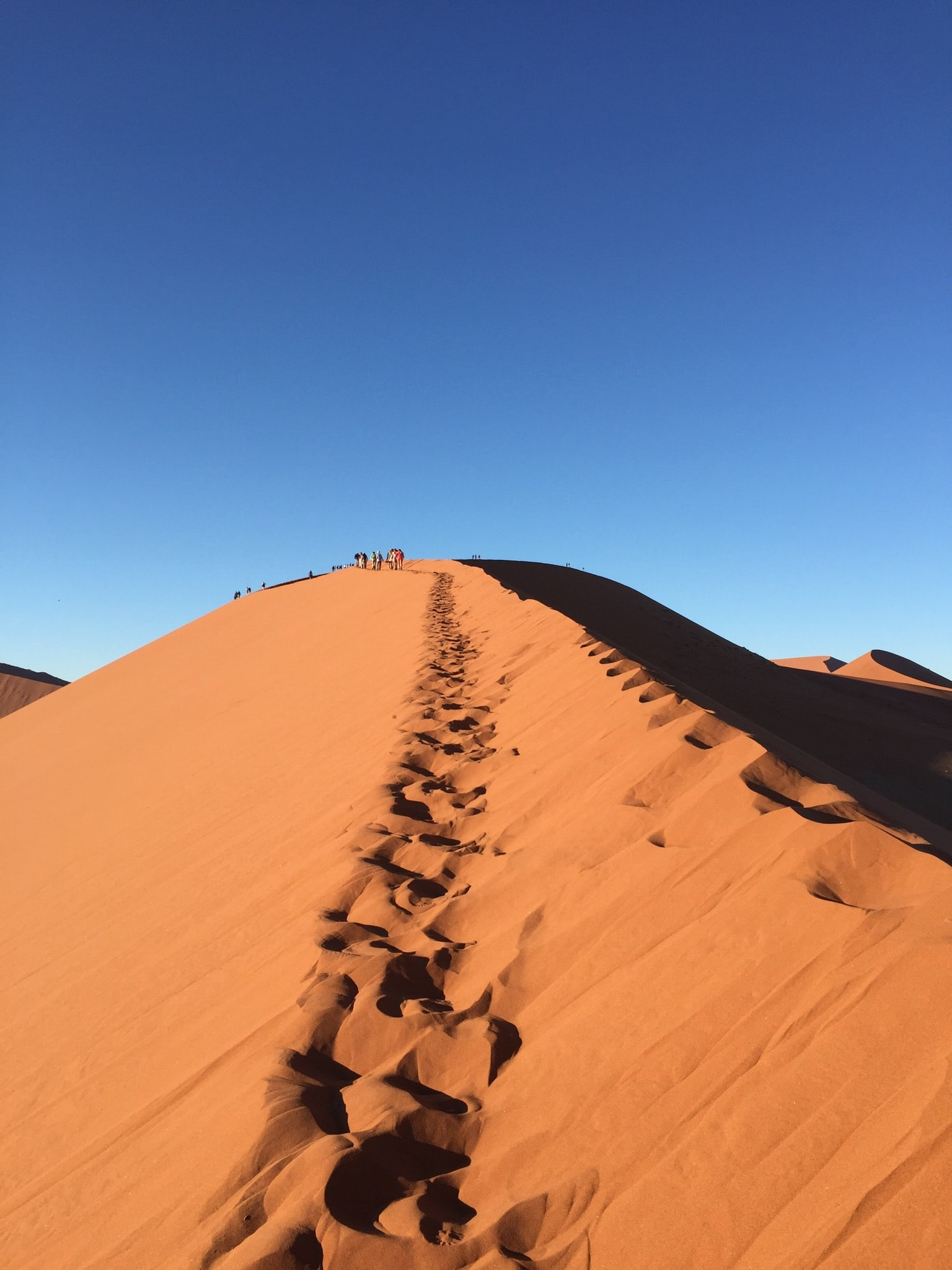 photo of foot prints on desert hill during daytime