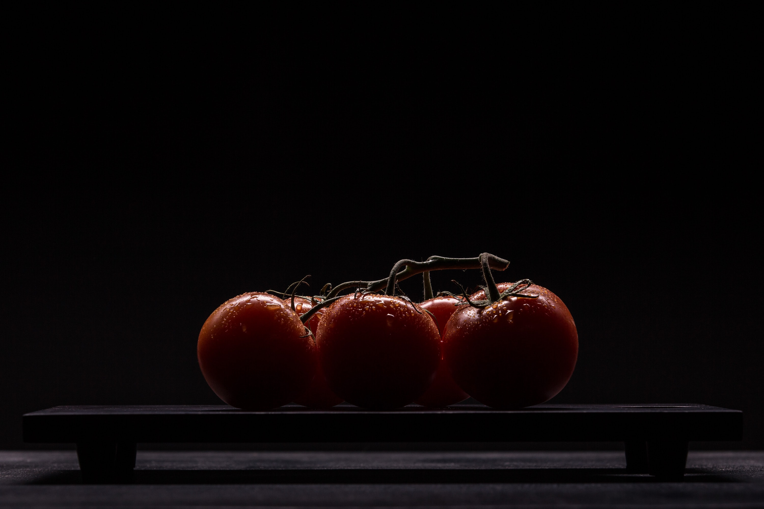 red tomatoes on black surface