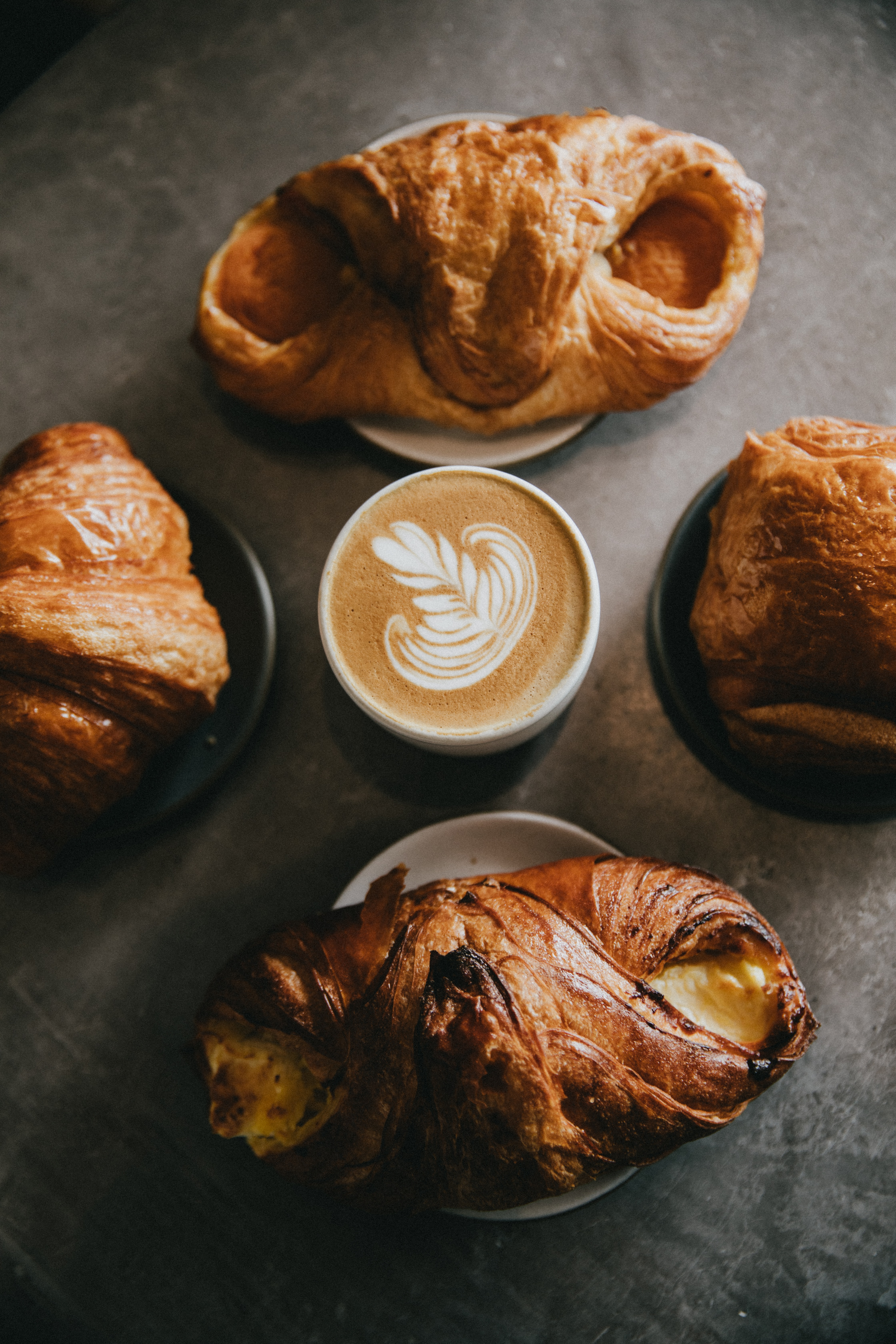 coffee surrounded by four baked breads
