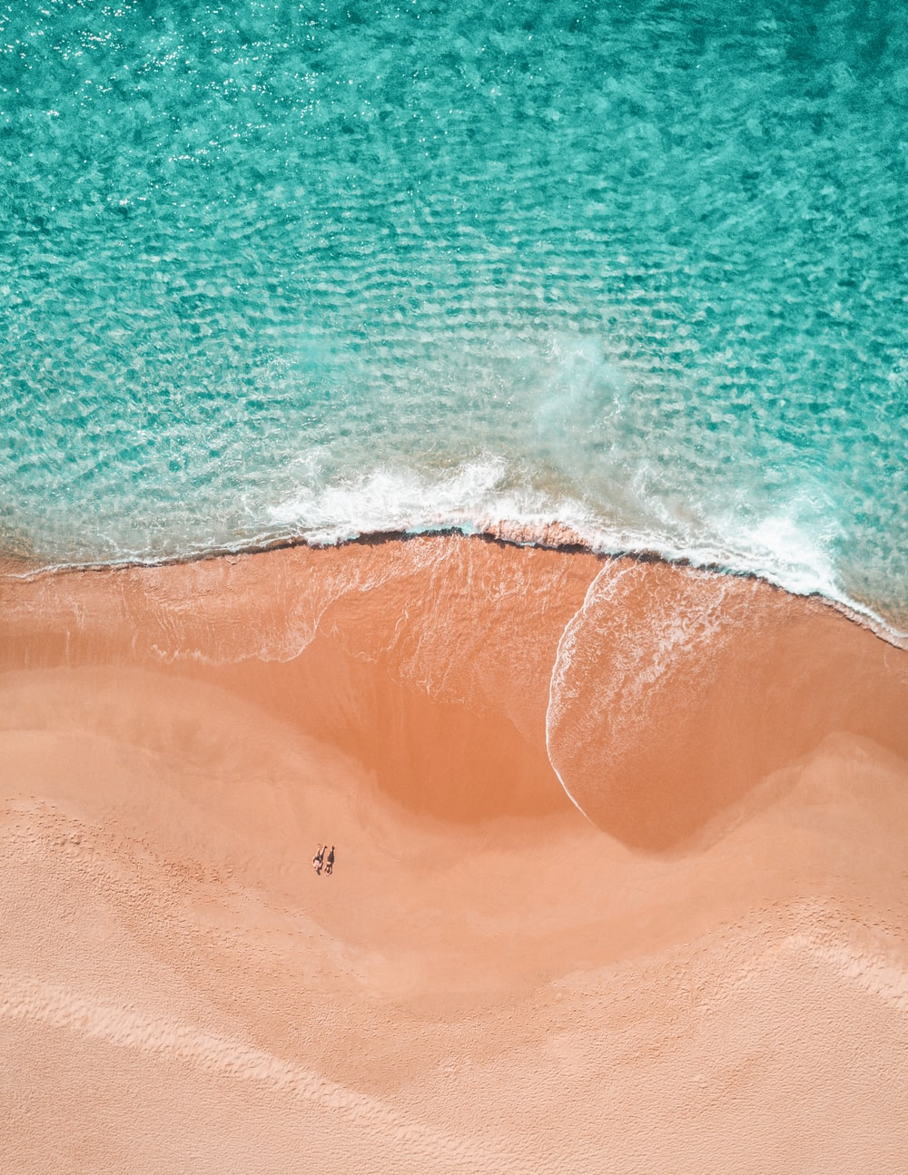 aerial photography of two person sunbathing on seashore