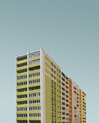 low-angle photography of white, green, pink, and brown concrete buildings