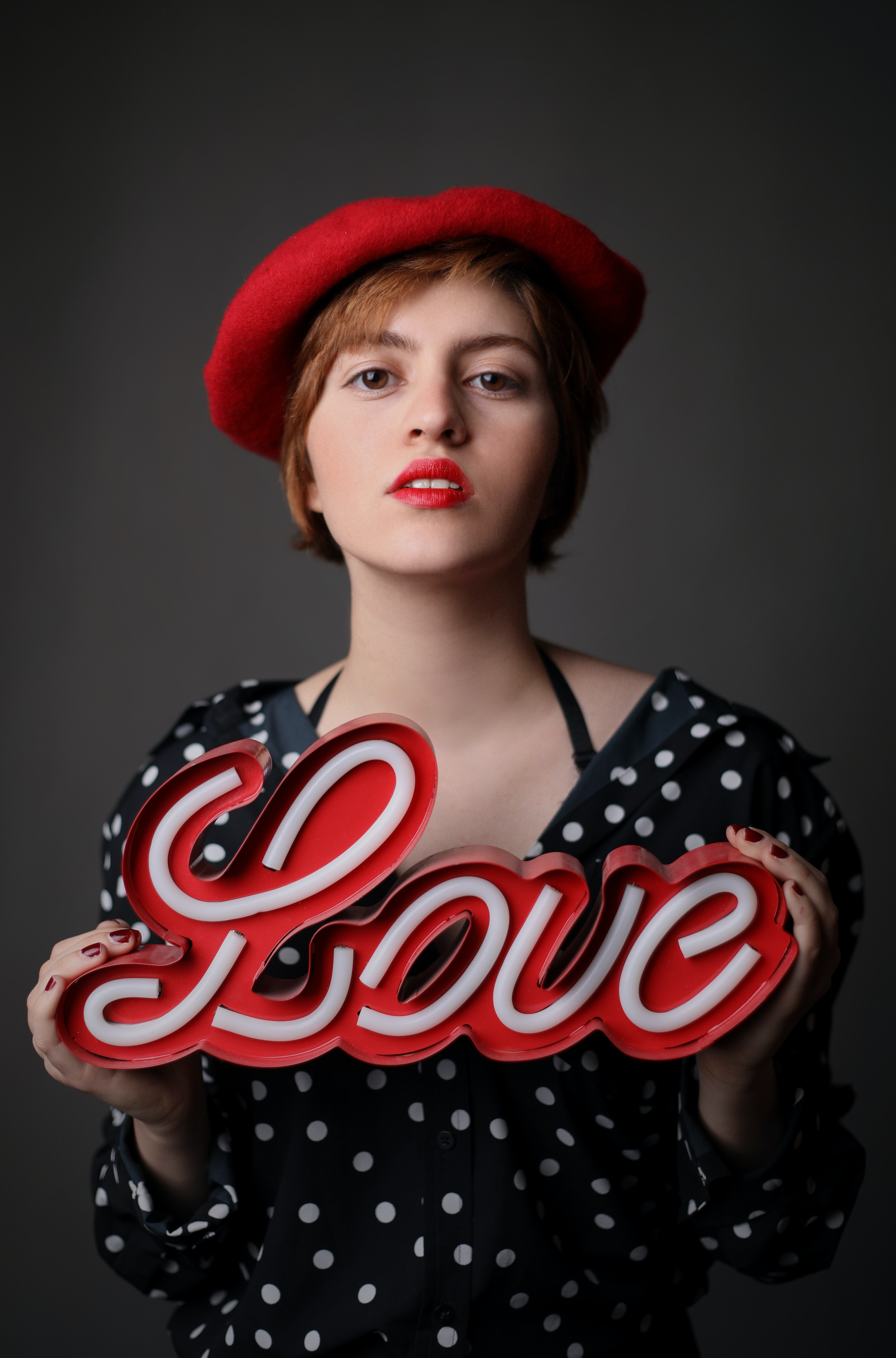 woman wearing black and white polka-dot top holding love freestanding letter