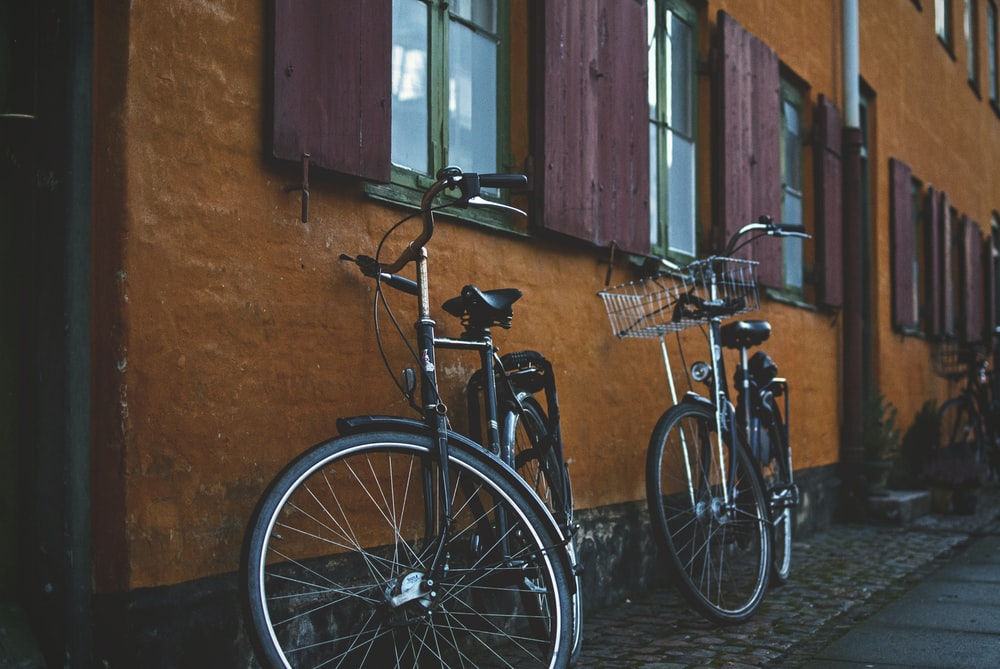 two black city bikes on brown concrete wall