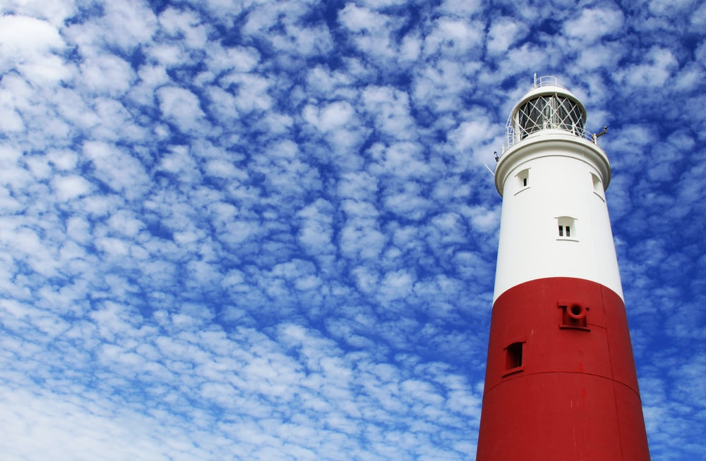 white and red lighthouse under cloudy sky