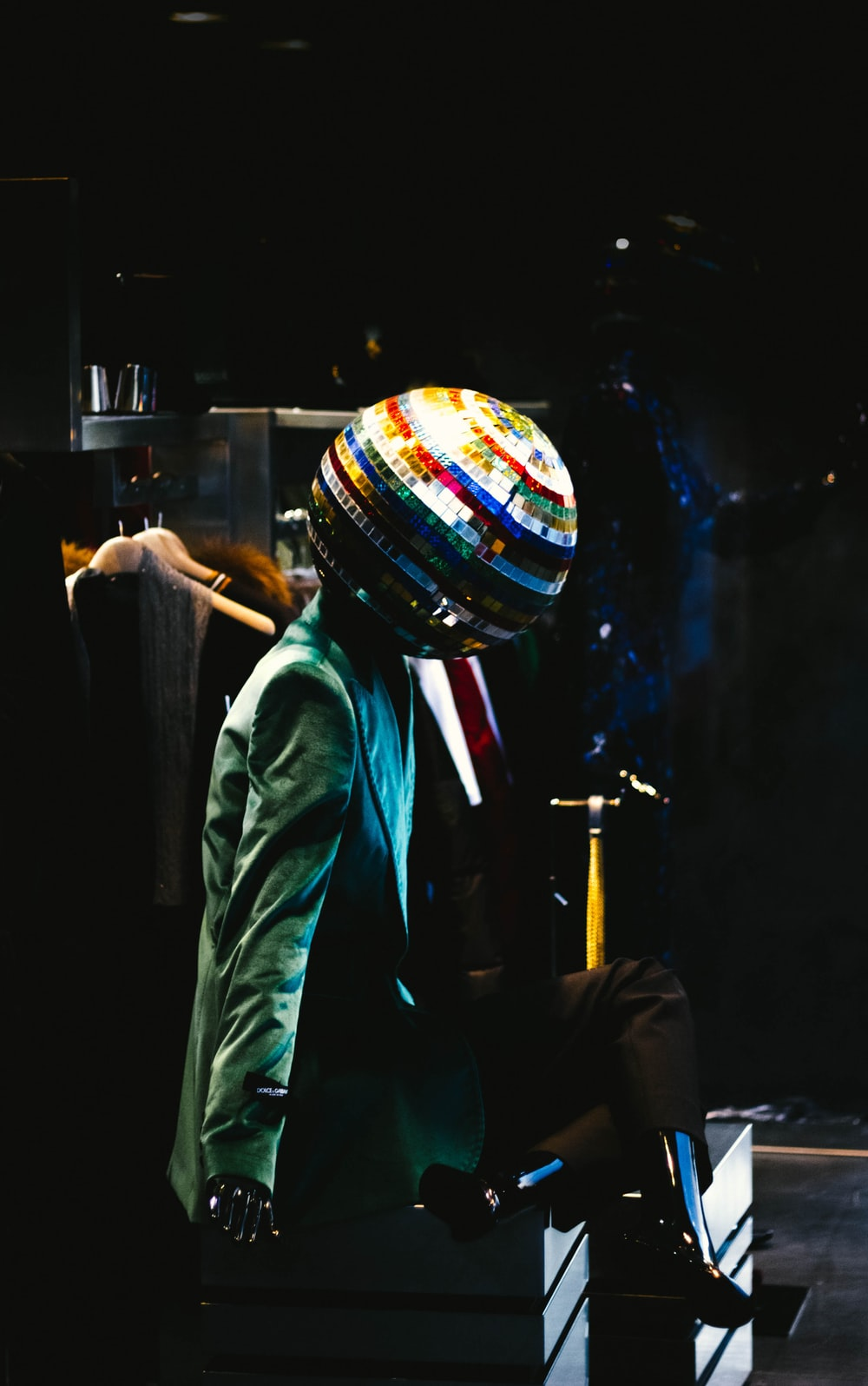 person wearing green blazer and disco ball head costume