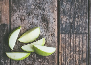 five green apple slices on brown wooden panel