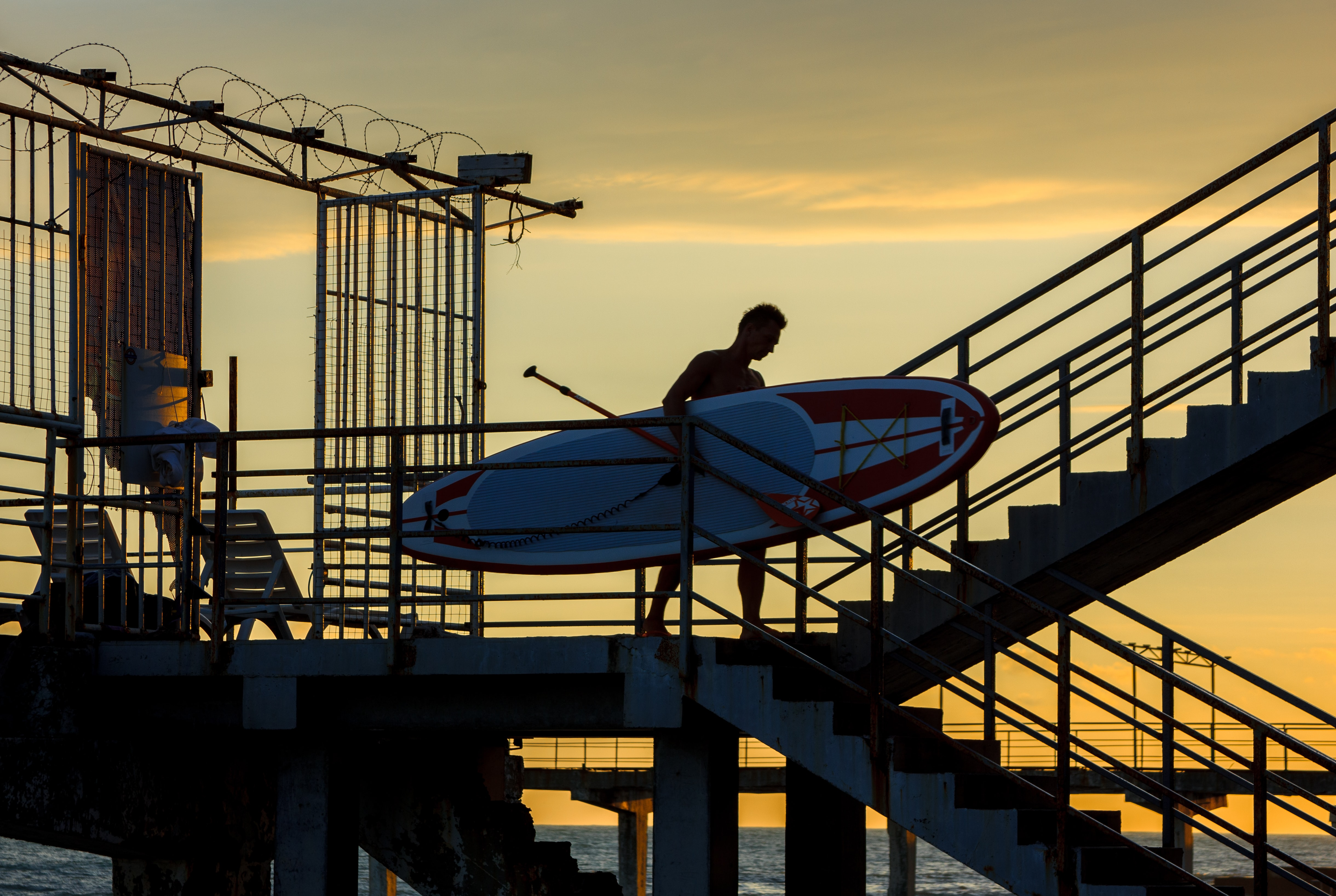 man holding paddle board during golden hour