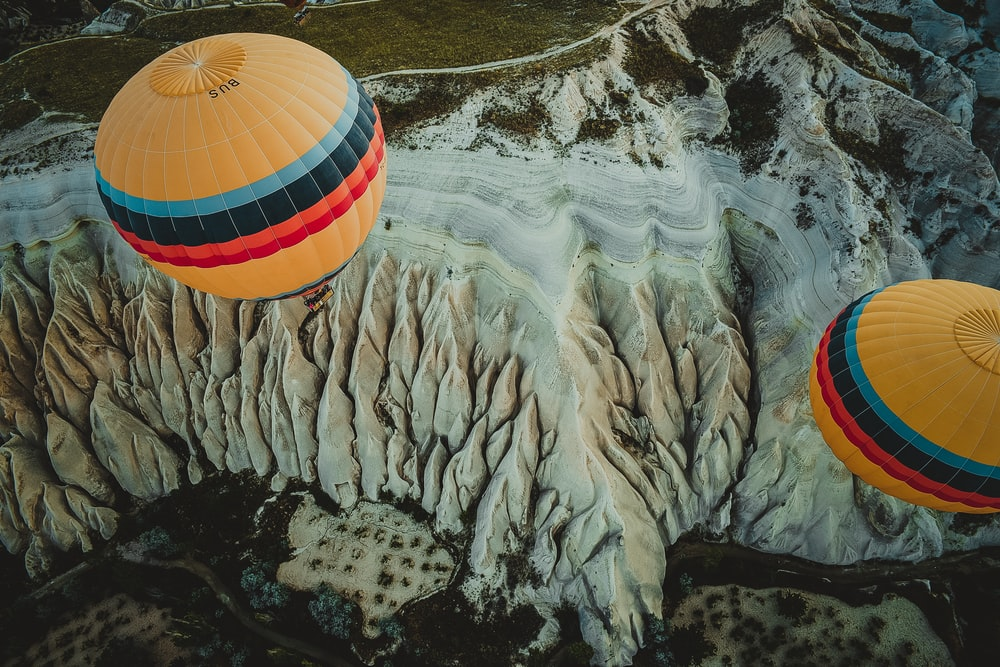 two yellow-red-black-teal hot air balloons floating over terrain