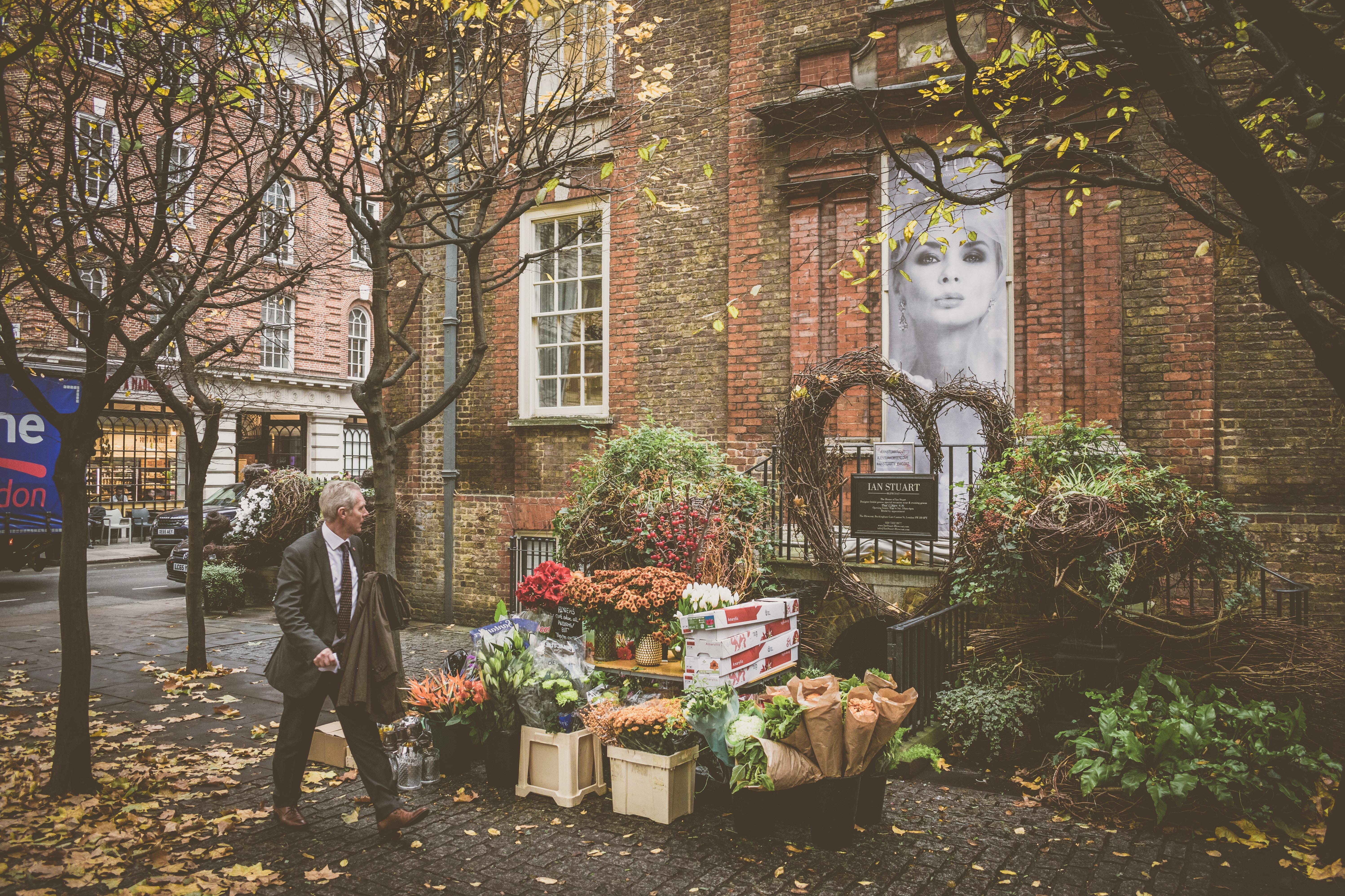 man walking beside flowershop