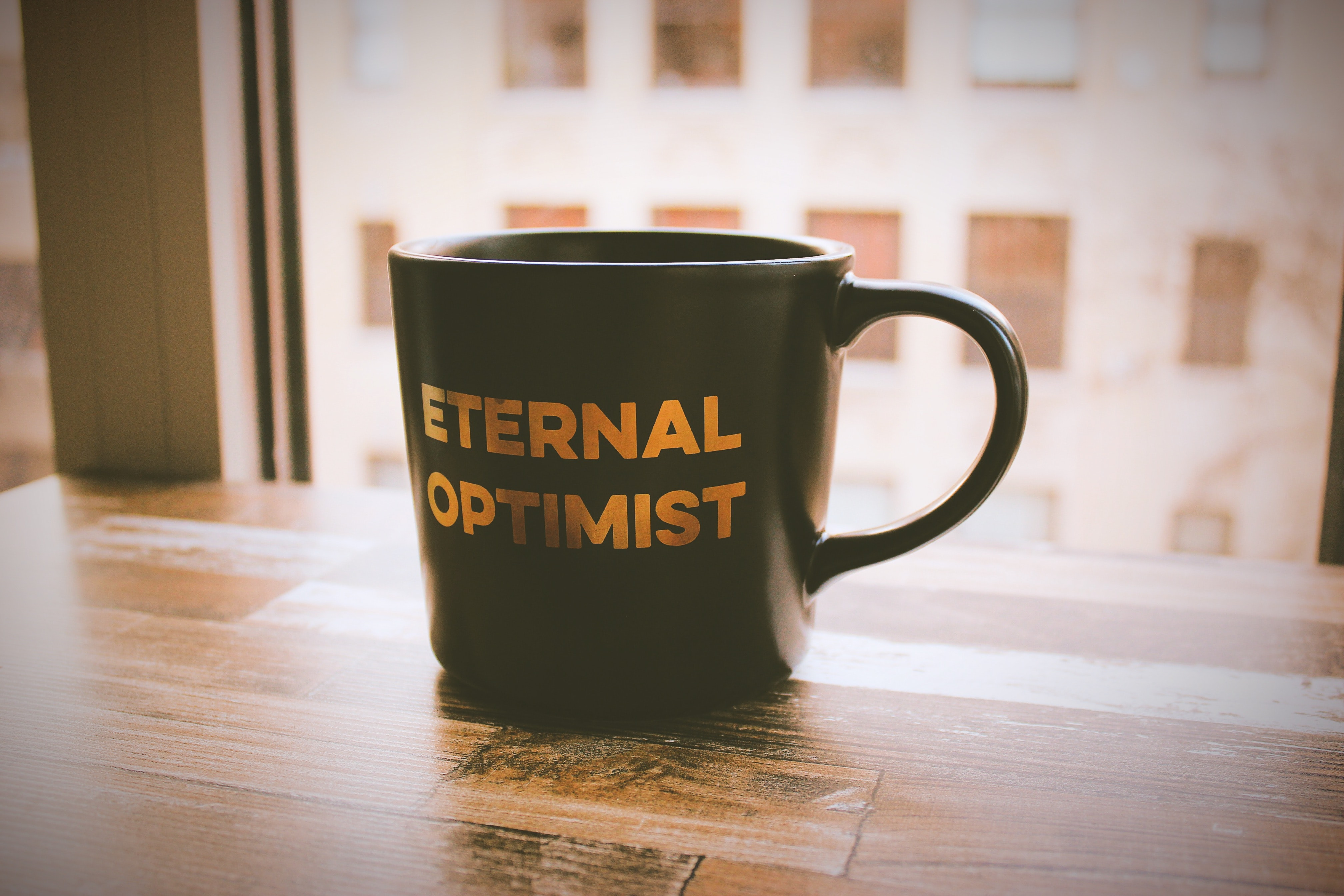 black and gold eternal and optimist painted ceramic cup on brown wooden panel beside glass window