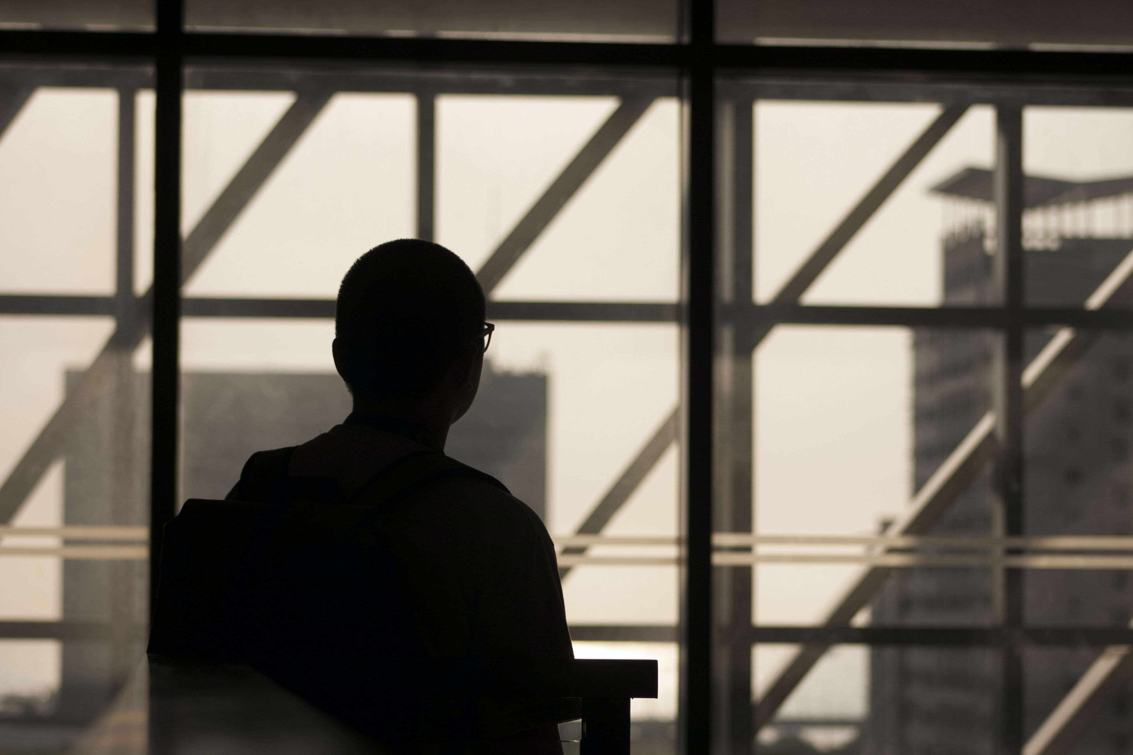 silhouette photo of man wearing eyeglasses sitting on chair