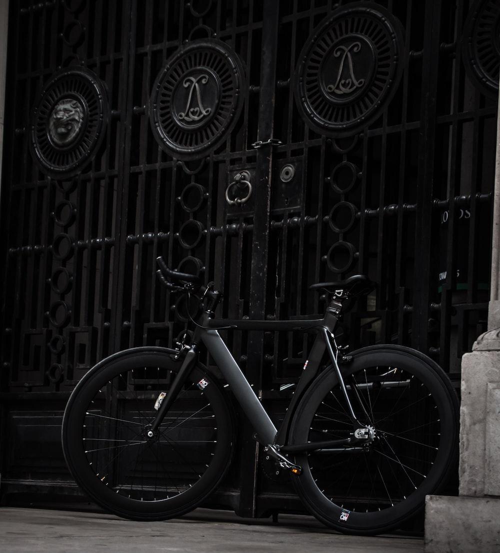 black fixed-gear bike leaning on black steel gate