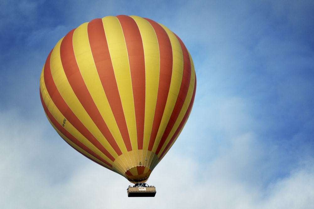 low angle photography of yellow and red stripe hot air balloon