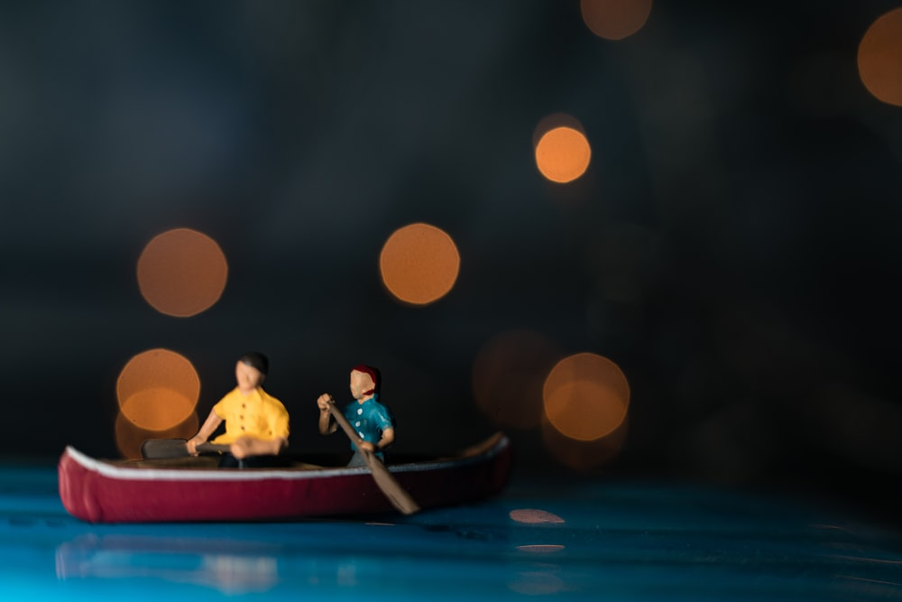 bokeh photography of two men riding canoe scale model