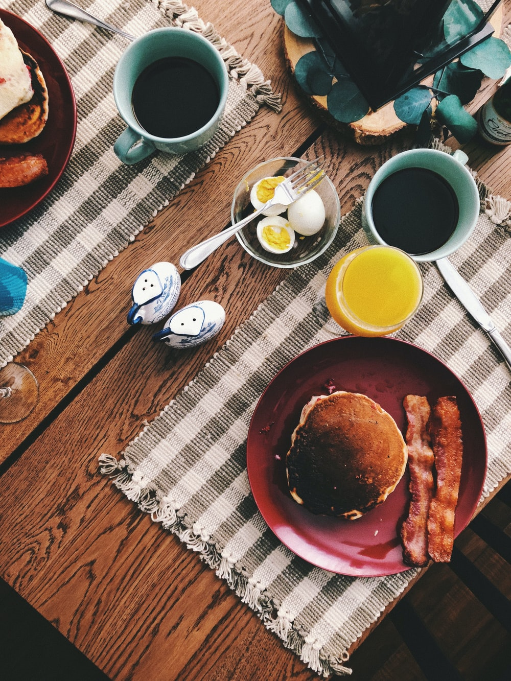 baked bread on round red ceramic plate near glass of orange juice, cup of coffee, and boiled eggs