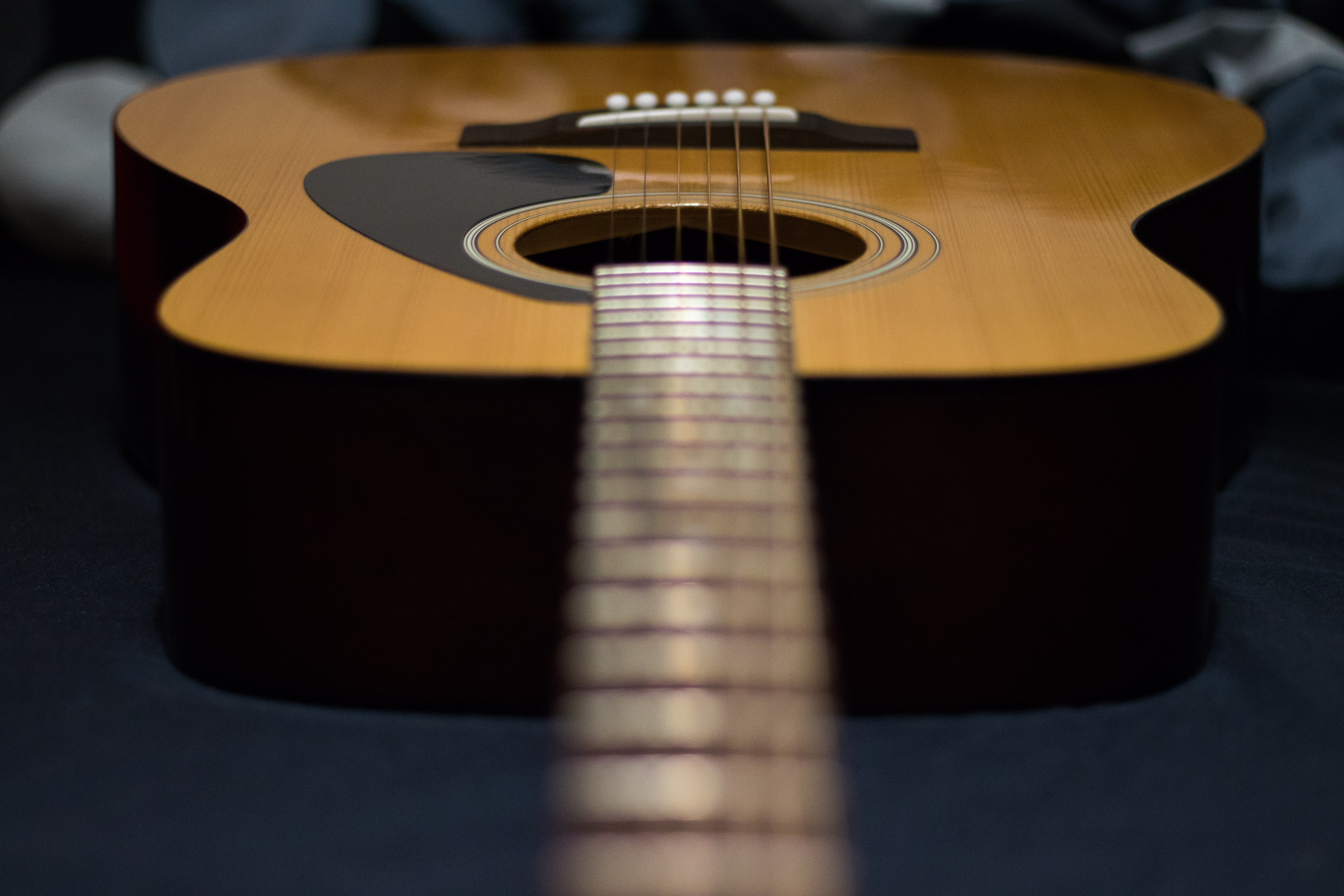 tilt-shift photography of brown acoustic guitar