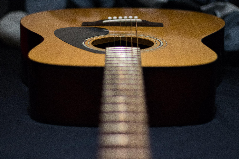 tilt-shift photography of brown acoustic guitar