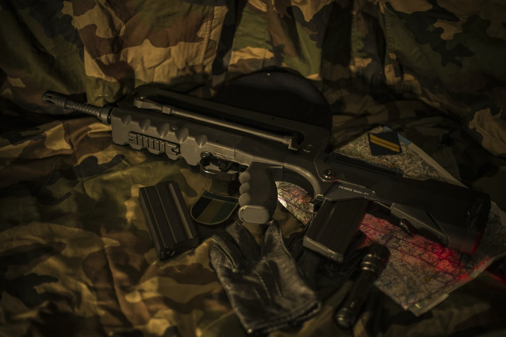black FAMAS lying on brown camouflage textile