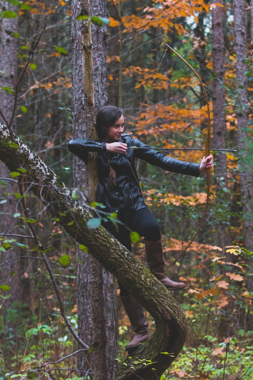 woman in black jacket holding longbow