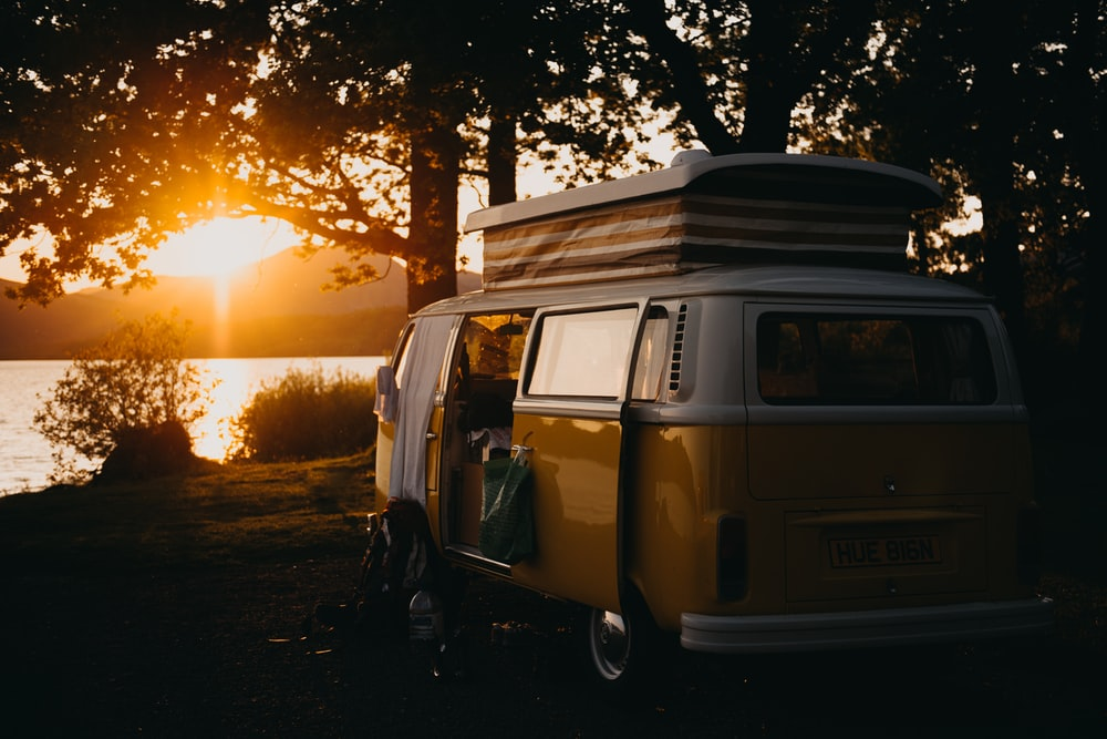 brown van under the tree during sunset