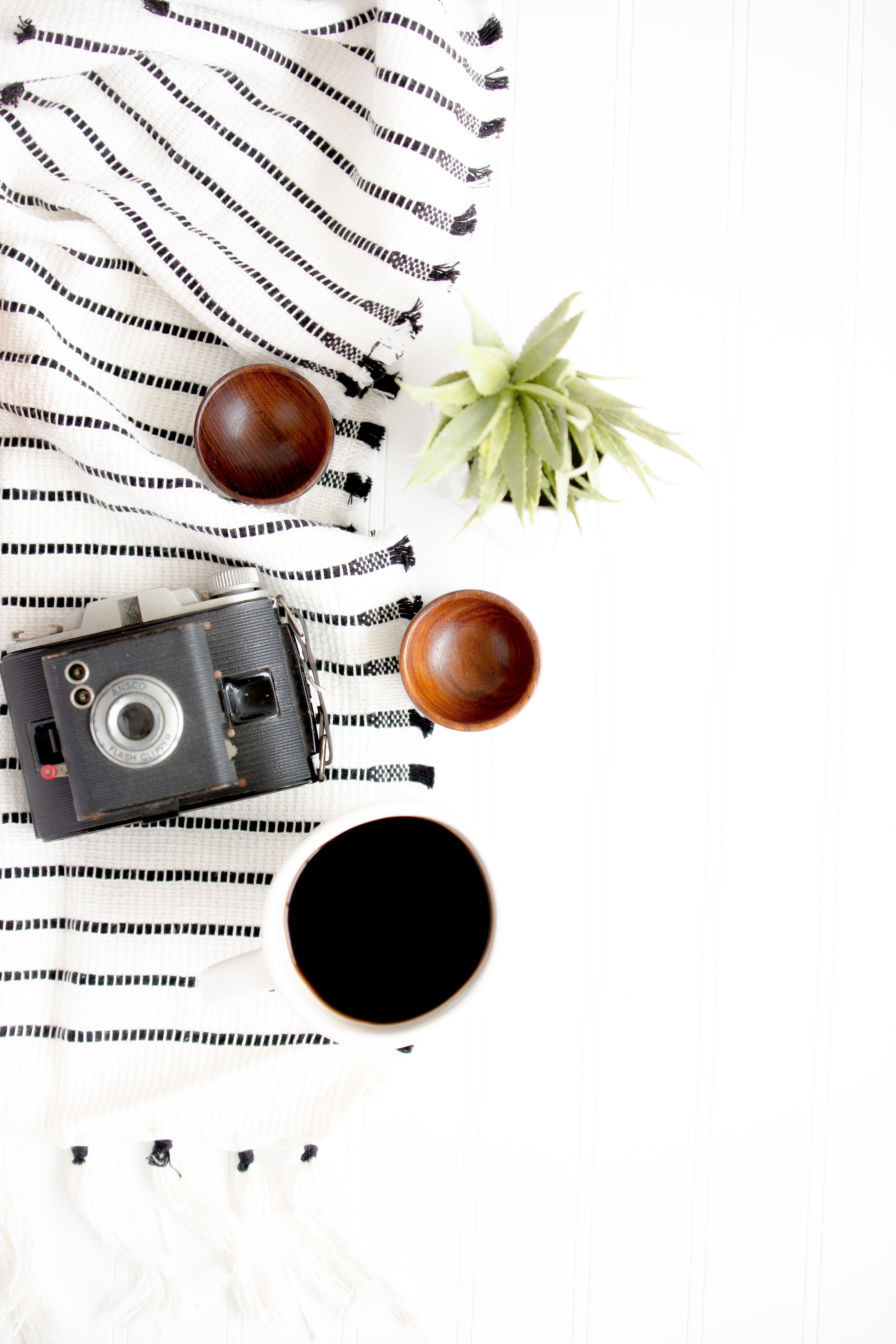 black and gray camera beside on brown wooden bowls